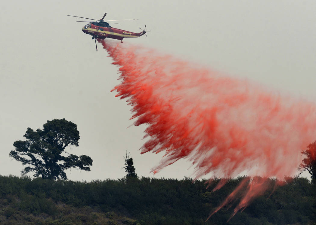 FILE - In this Aug. 13, 2016 file photo, a fire attack helicopter makes a retardant drop during a firing operation on the ridge between Mount Manuel and the Coast Ridge Road while fighting the Sob ...