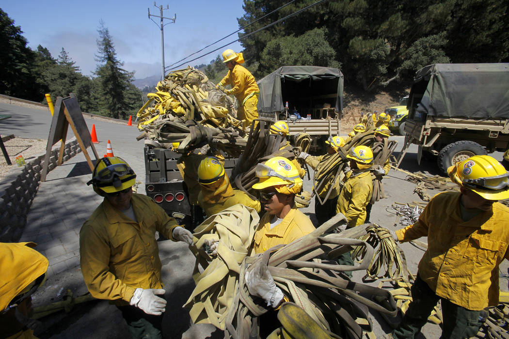 FILE - In this Aug. 6, 2016 file photo, members of the California National Guard help load about 5 miles of used wildland fire hose in Palo Colorado Canyon, south of Monterey Calif., during effort ...