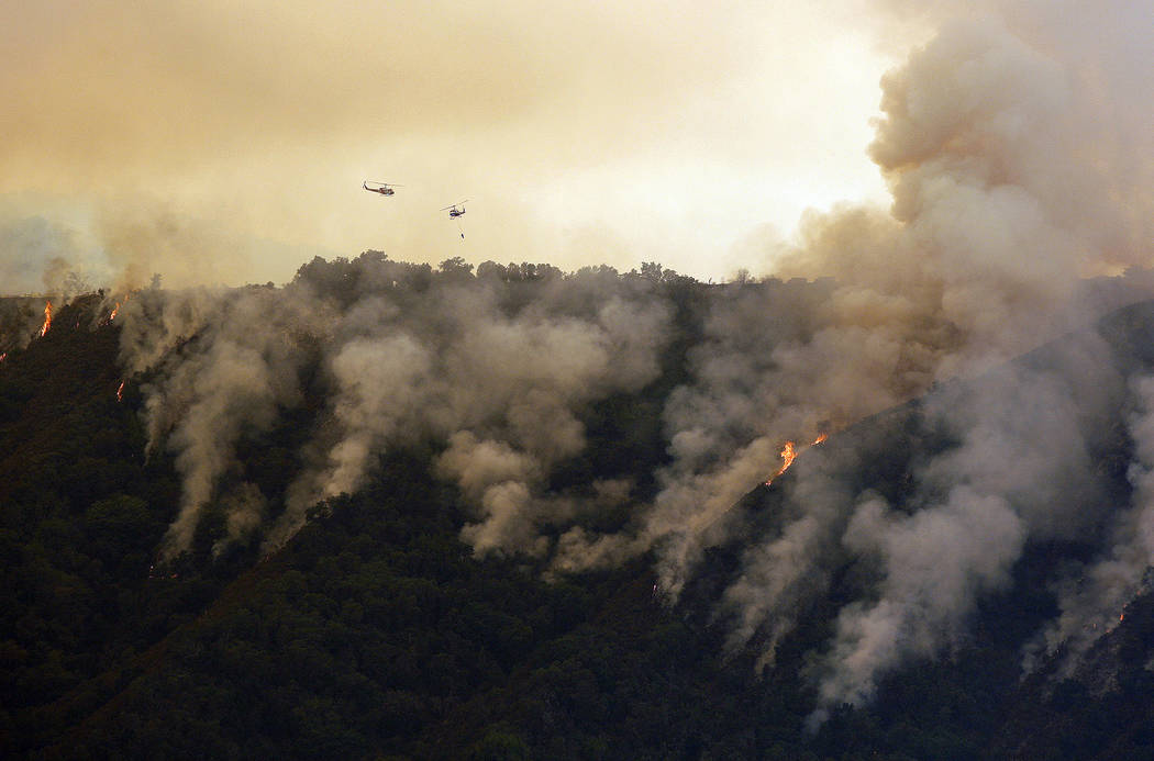 FILE - In this Aug. 2, 2016, file photo, helicopters fight the Soberanes Fire west of Cachagua, Calif. When a fire burned across Big Sur two years ago and threatened hundreds of homes scattered on ...