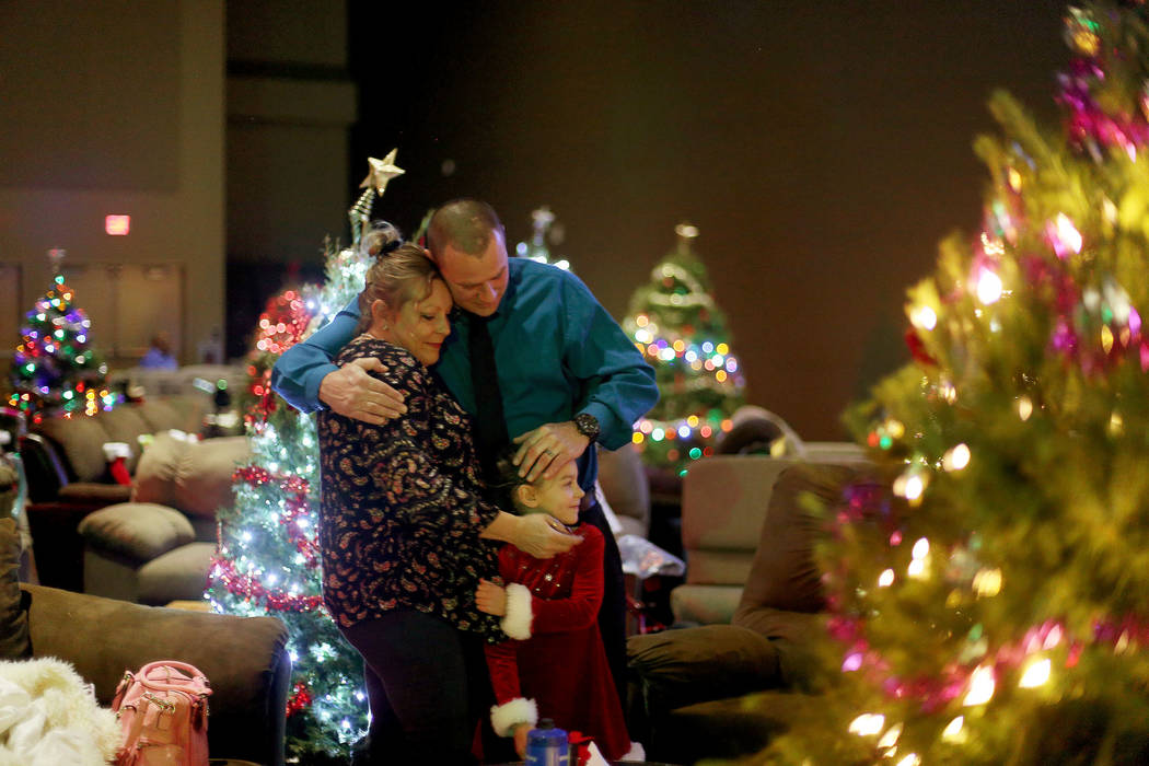 """Kellie Beck, from left, hugs her husband Jerod Beck and their daughter Savanna beck, 5, at an event hosted by HOPE for Prisoners and the Nevada Department of Corrections that set up 50 """"livin ..."""