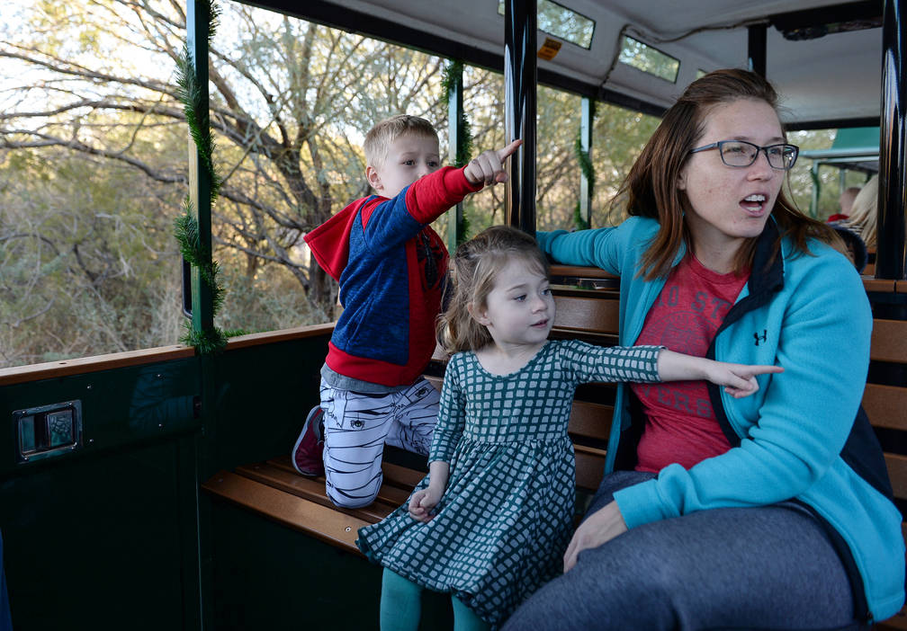 James Aukeman, 5, left, Eliza Aukeman, 3, and Julianne Aukeman from Las Vegas look out as they take a train ride as Springs Preserve hosts its Holiday Express in Las Vegas, Sunday, Dec. 16, 2018. ...