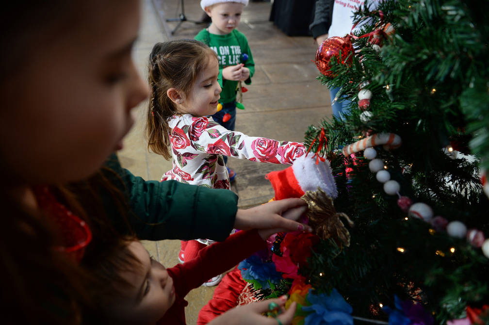 Gabriella Ordway, 2, from Las Vegas places an ornament on a Christmas tree at a village winter wonderland as Springs Preserve hosts its Holiday Express in Las Vegas, Sunday, Dec. 16, 2018. Carolin ...