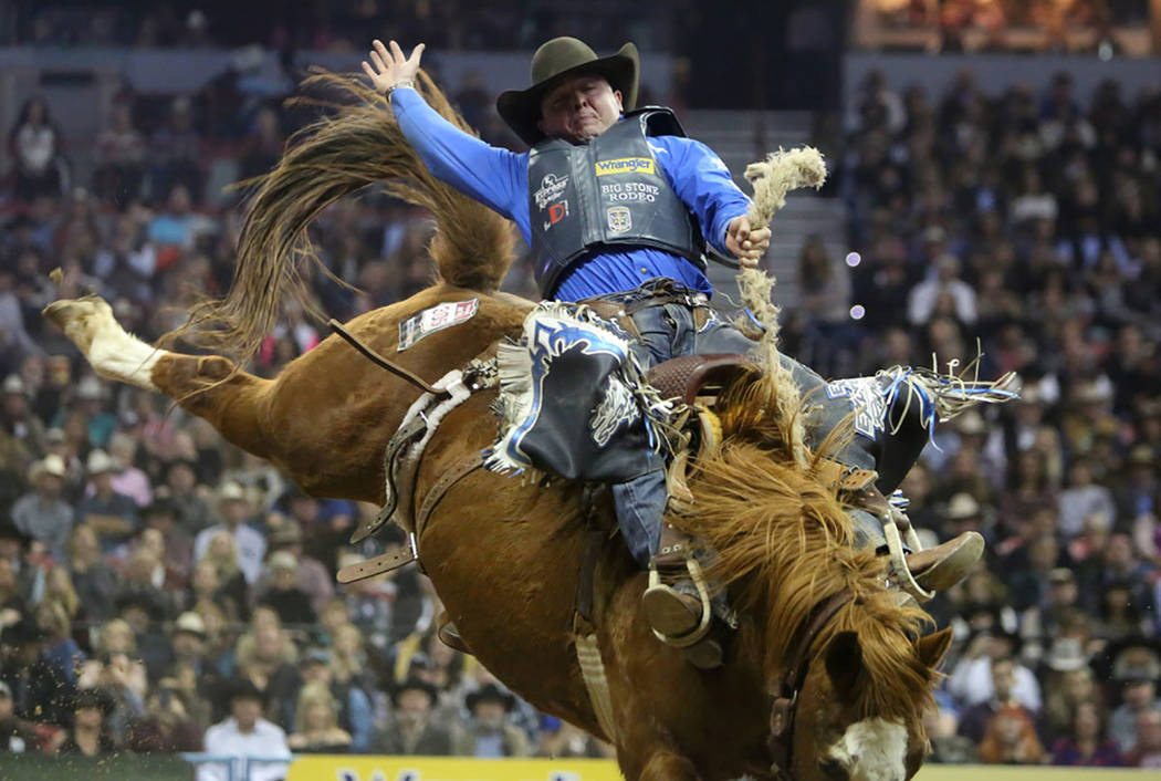 Jake Wright of Milford, Utah competes in the saddle bronc riding event during the tenth go-round of the National Finals Rodeo at the Thomas & Mack Center in Las Vegas, Saturday, Dec. 15, 2018. ...