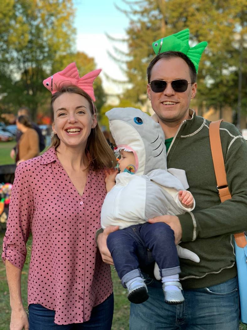 """This image released by Jason Simms shows him with his wife Jillian and their daughter Fionnuala wearing a shark costume on the Town Green in Madison, Conn. Fionnuala first heard the """"Baby Sh ..."""