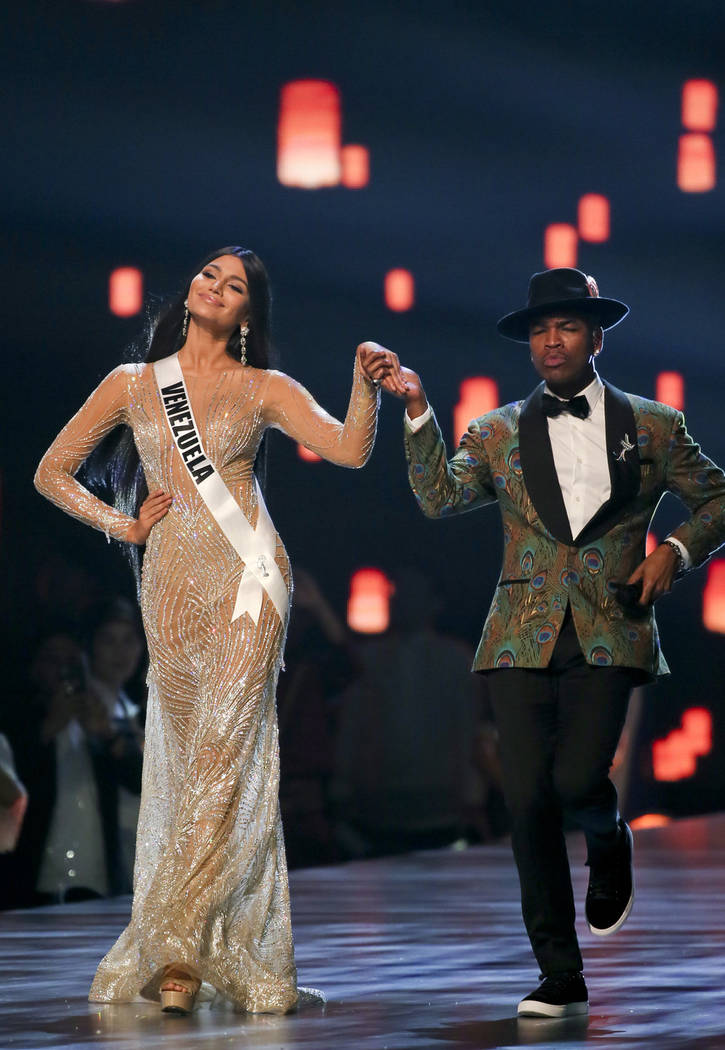 Singer Ne-Yo leads Miss Venezuela Sthefany Gutierrez during the final round of the 67th Miss Universe competition in Bangkok, Thailand, Monday, Dec. 17, 2018.(AP Photo/Gemunu Amarasinghe)