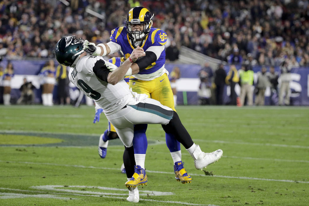 Philadelphia Eagles quarterback Nick Foles throws under pressure from Los Angeles Rams defensive end Aaron Donald during the first half in an NFL football game Sunday, Dec. 16, 2018, in Los Angele ...