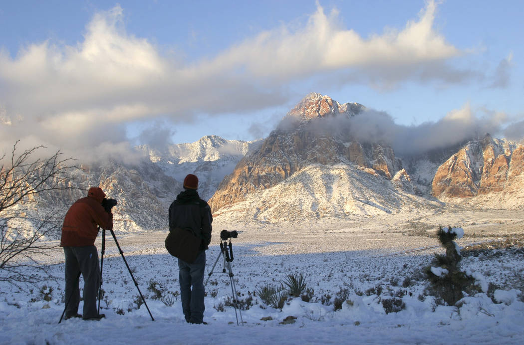 Photographers gather at the Red Rock Overlook on state Route 159 to capture images of the snow-covered mountains of Red Rock Canyon National Conservation Area in the early morning on Dec. 19, 2008 ...