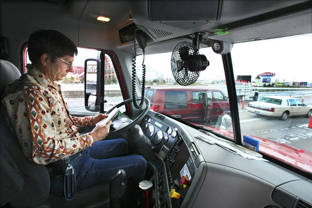 Tractor-trailer truck driver Gary Mott catches up on his reading on Interstate 15 in Primm on Dec. 18, 2008, after the interstate was closed due to the winter storm that passed through the area. ( ...