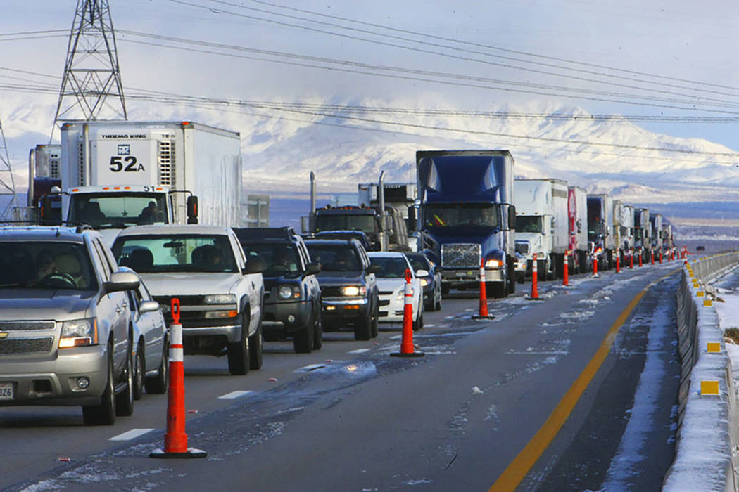 A line of semi tractor-trailers and other vehicles are parked on Interstate 15 in Primm on Dec. 18, 2008, after the interstate was closed due to the winter storm that passed through the area. (Las ...