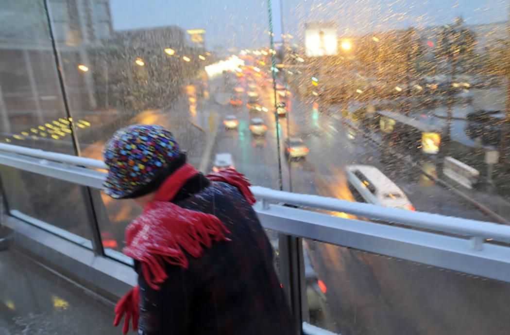 A woman bundled up braves the freezing rain and snow as she crosses one of the pedestrian bridges along the Las Vegas Strip on Dec. 17, 2008. (Las Vegas Review-Journal)
