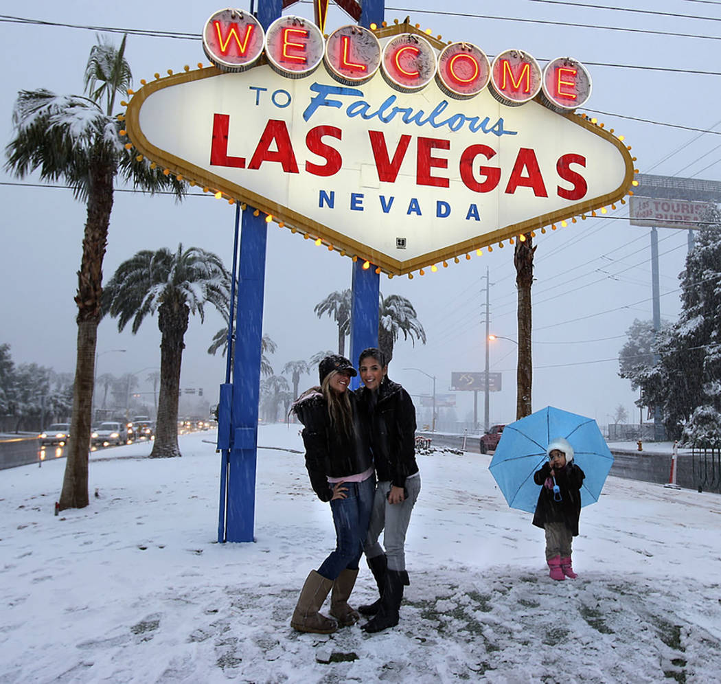 Visitors have their picture taken at the welcome sign during a snowstorm on the Las Vegas Strip on Dec. 17, 2008. (Las Vegas Review-Journal)