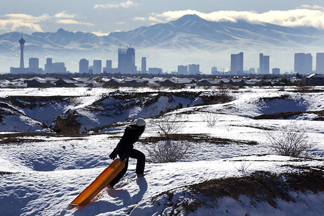 With the Las Vegas skyline looming in the background, Kymberlee Nguyen makes her way to the top of a hill while sledding in a desert region near North Durango Road on Dec. 18, 2008. (Las Vegas Rev ...