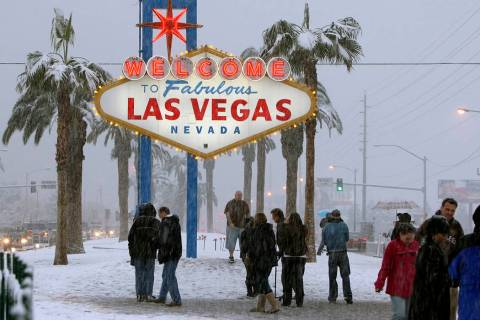 People visit the welcome sign on the Las Vegas Strip to take photos as snow fell in Las Vegas, ...