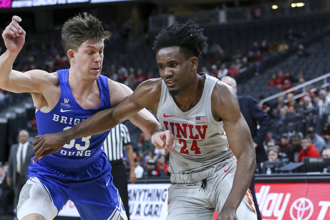 UNLV Rebels forward Joel Ntambwe (24) dribbles the ball as Brigham Young Cougars forward Dalton Nixon (33) defends during the first half of an NCAA college basketball game at T-Mobile Arena in Las ...