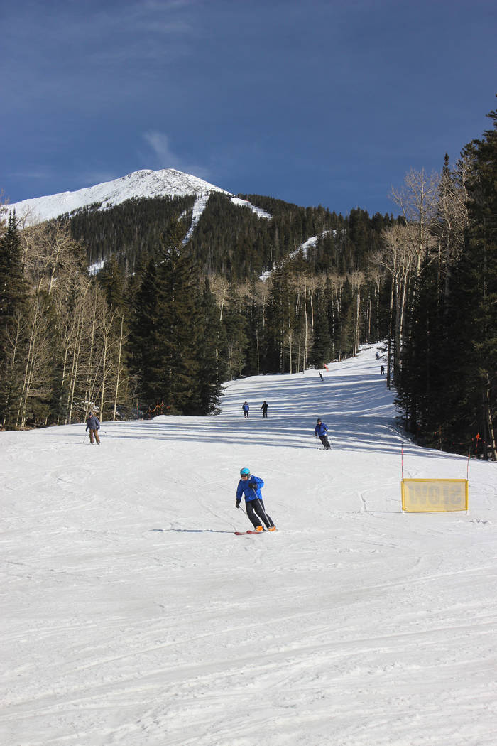 Skiers at Arizona Snowbowl, located at the base of the San Francisco Peaks just outside of Flagstaff, Arizona. Above the slopes is Agassiz Peak; at 12, 356 feet it is one of the highest in the sta ...