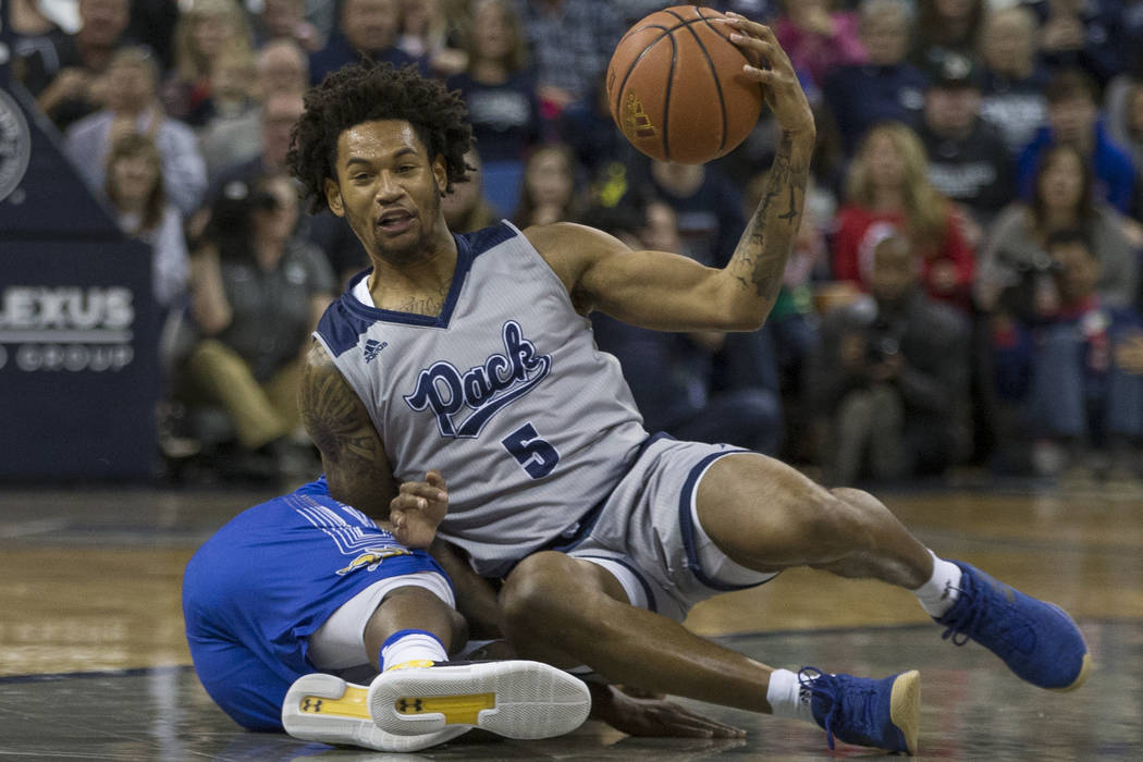 Nevada guard Nisre Zouzoua (5) scrambles for a loose ball against South Dakota State in the second half of an NCAA college basketball game in Reno, Nev., Saturday, Dec. 15, 2018. (AP Photo/Tom R. ...