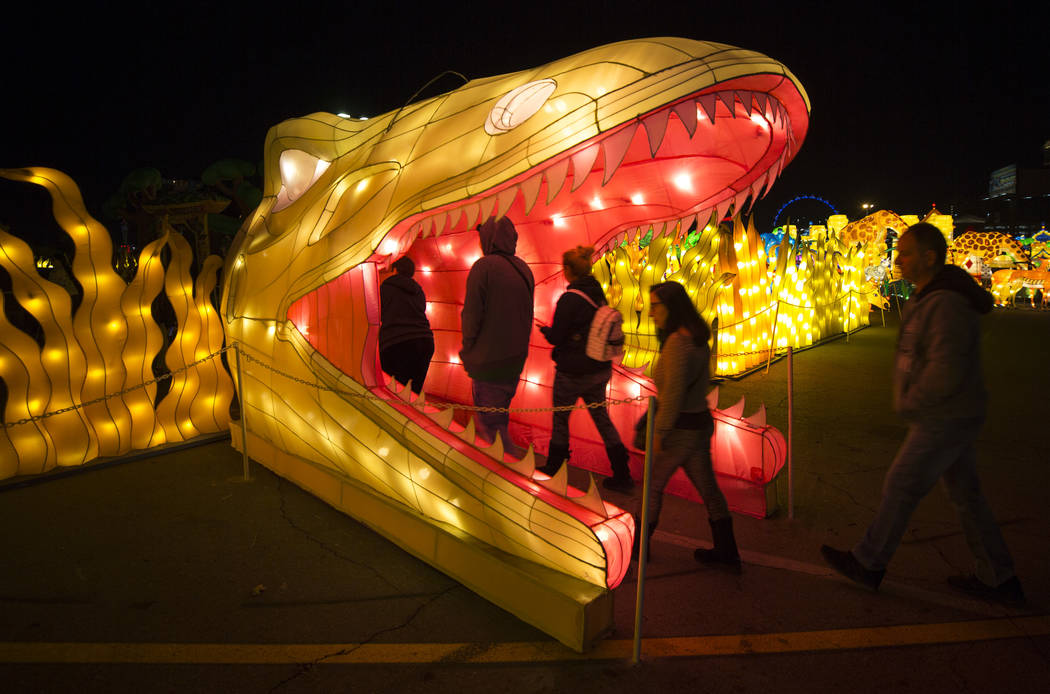 People walk through an illuminated dinosaur head at the Animal Kingdom display at the Global Winter Wonderland lantern festival at the Rio in Las Vegas on Wednesday, Dec. 19, 2018. Richard Brian L ...