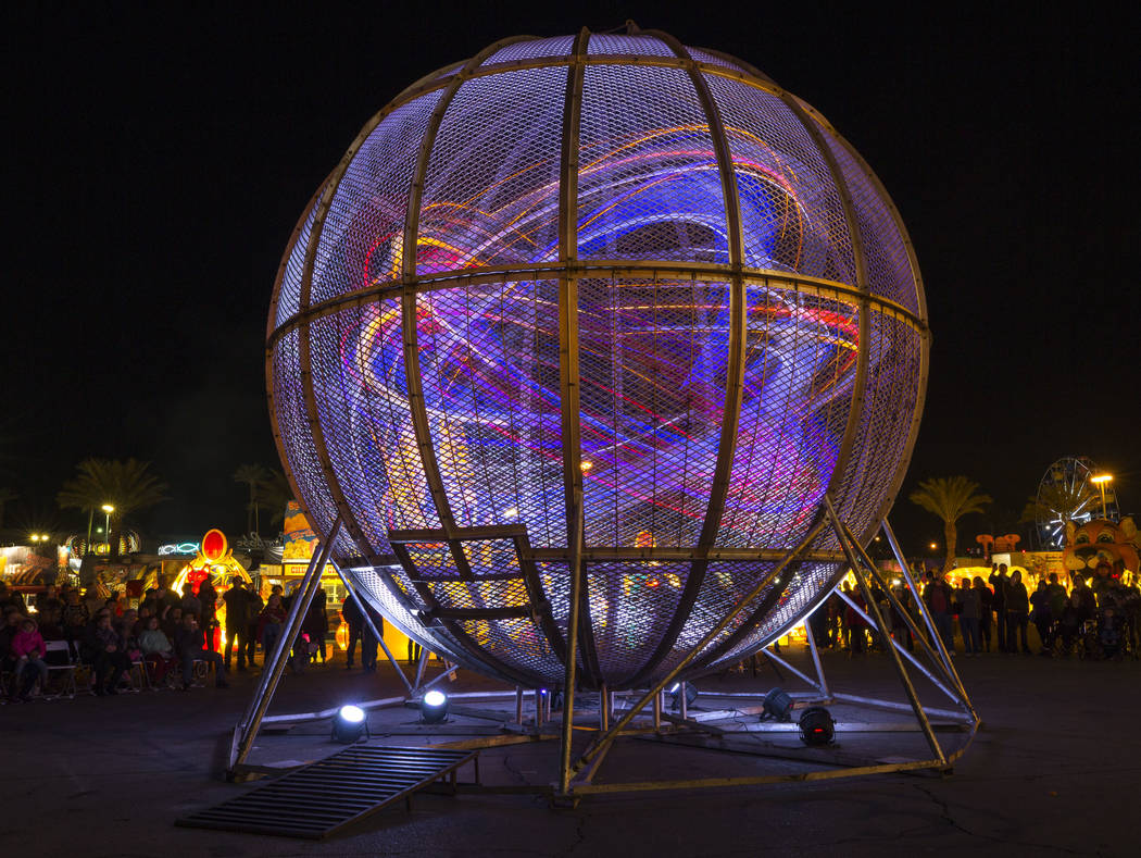 Wrapped in colored LED rope lights, five stunt motorcyclist perform in the Globe of Death during the Global Winter Wonderland lantern festival at the Rio in Las Vegas on Wednesday, Dec. 19, 2018. ...