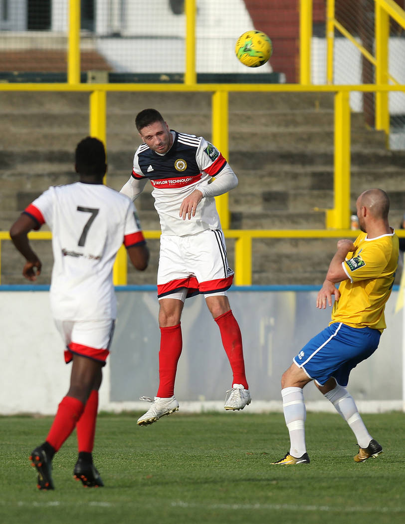 Cray Wanderers defender Jay Leader (4), center, heads the soccer ball as Sean Roberts (7) moves in against the Canvey Island Gulls in Canvey Island, Essex, England, Saturday, Oct. 13, 2018. Heidi ...