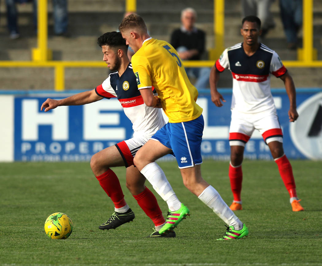 Cray Wanderers striker Freddie Parker (9), left, moves the soccer ball past Canvey Island Gulls George Allen (5) during a game in Canvey Island, Essex, England, Saturday, Oct. 13, 2018. Heidi Fang ...