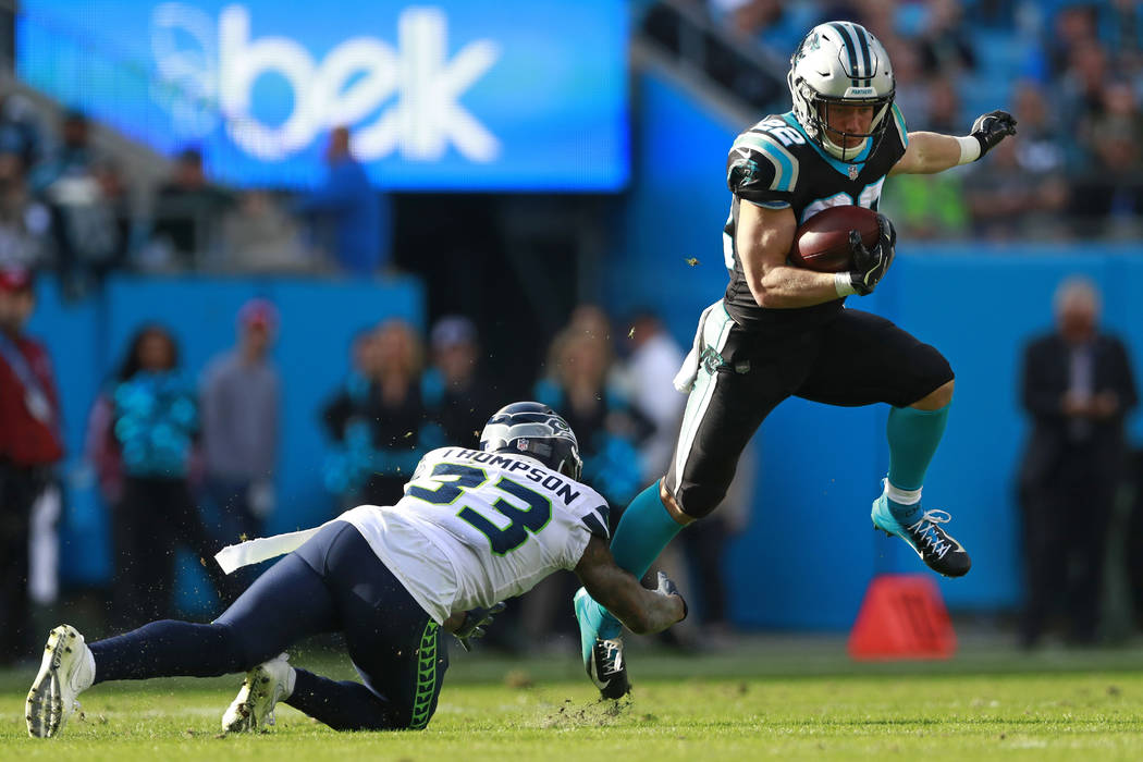 In this Nov. 25, 2018, file photo, Carolina Panthers' Christian McCaffrey (22) avoids the tackle of Seattle Seahawks' Tedric Thompson (33) during the first half of an NFL football game in Charlott ...