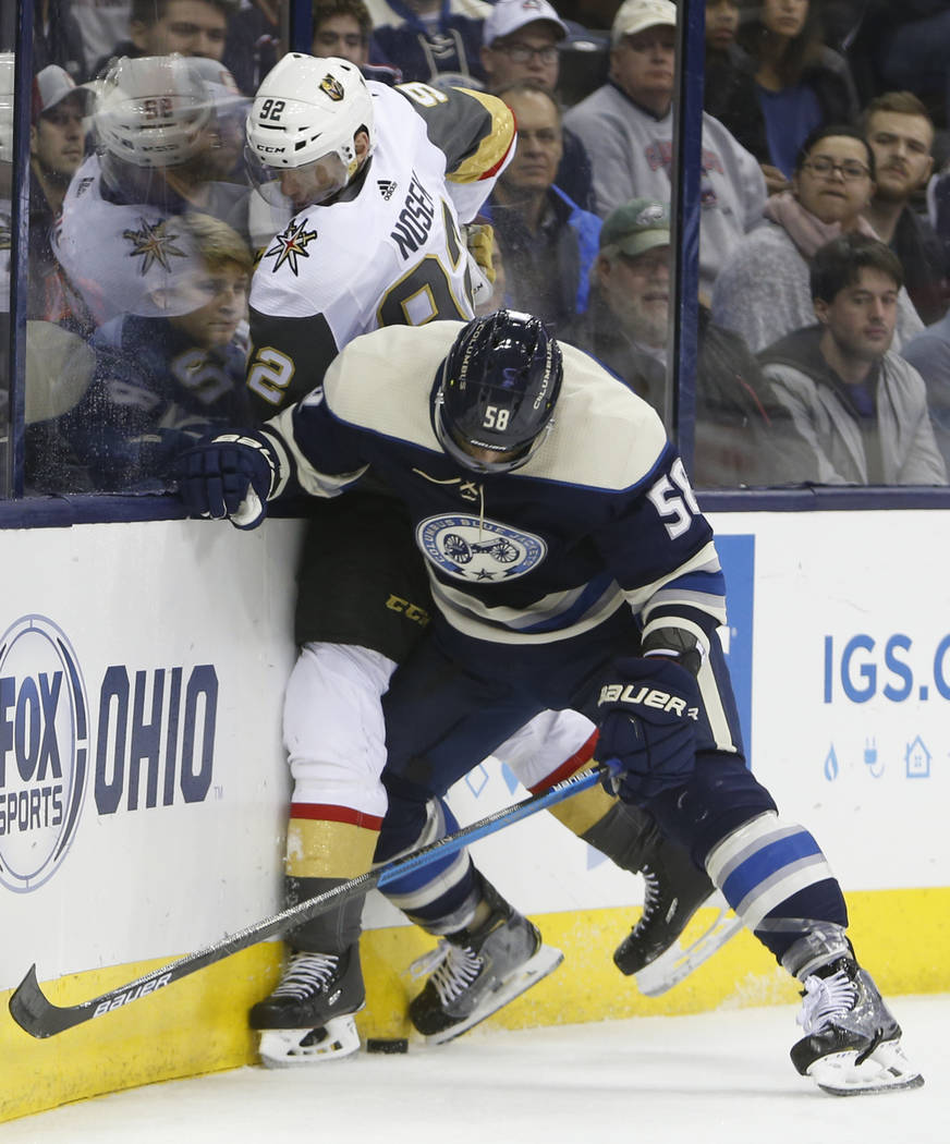 Columbus Blue Jackets' David Savard, right, checks Vegas Golden Knights' Tomas Nosek, of the Czech Republic, during the third period of an NHL hockey game Monday, Dec. 17, 2018, in Columbus, Ohio. ...
