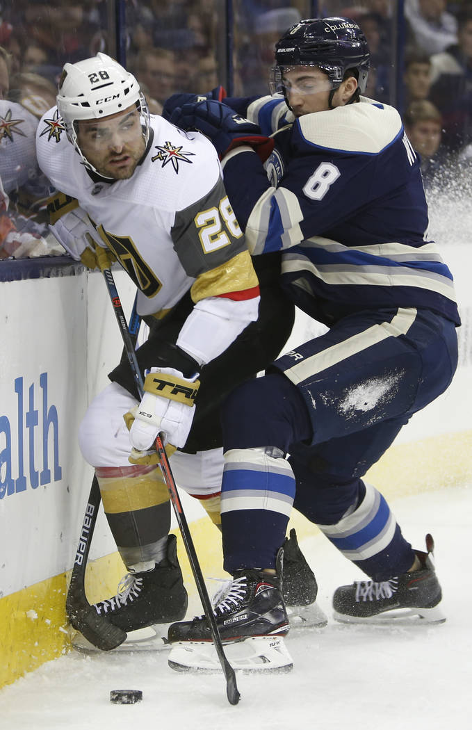 Vegas Golden Knights' William Carrier, left, looks for an open pass as Columbus Blue Jackets' Zach Werenski defends during the first period of an NHL hockey game Monday, Dec. 17, 2018, in Columbus ...