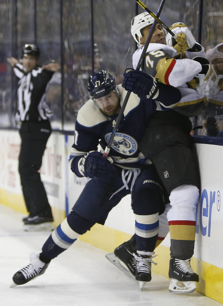 Columbus Blue Jackets' Brandon Dubinsky, left, checks Vegas Golden Knights' Ryan Reaves during the first period of an NHL hockey game Monday, Dec. 17, 2018, in Columbus, Ohio. (AP Photo/Jay LaPrete)