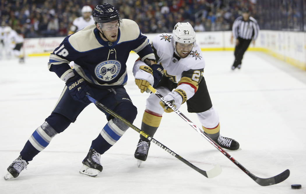 Columbus Blue Jackets' Pierre-Luc Dubois, left, and Vegas Golden Knights' Shea Theodore chase a loose puck during the first period of an NHL hockey game Monday, Dec. 17, 2018, in Columbus, Ohio. ( ...