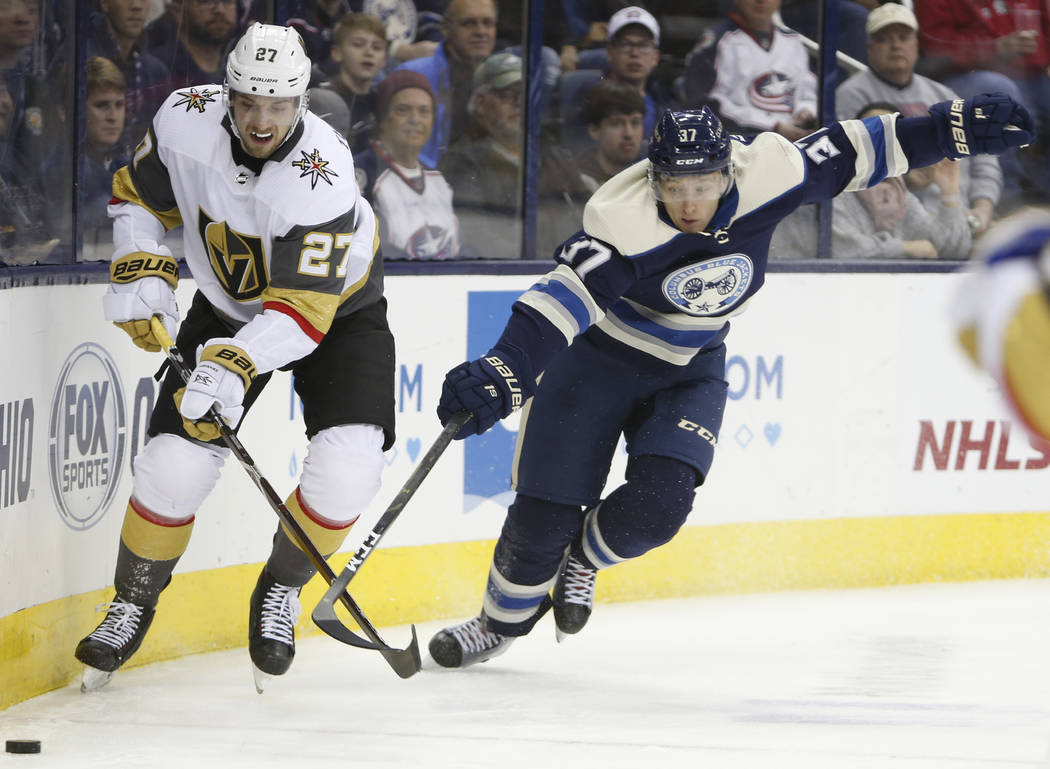 Vegas Golden Knights' Shea Theodore, left, clears the puck away from Columbus Blue Jackets' Markus Hannikainen, of Finland, during the second period of an NHL hockey game Monday, Dec. 17, 2018, in ...