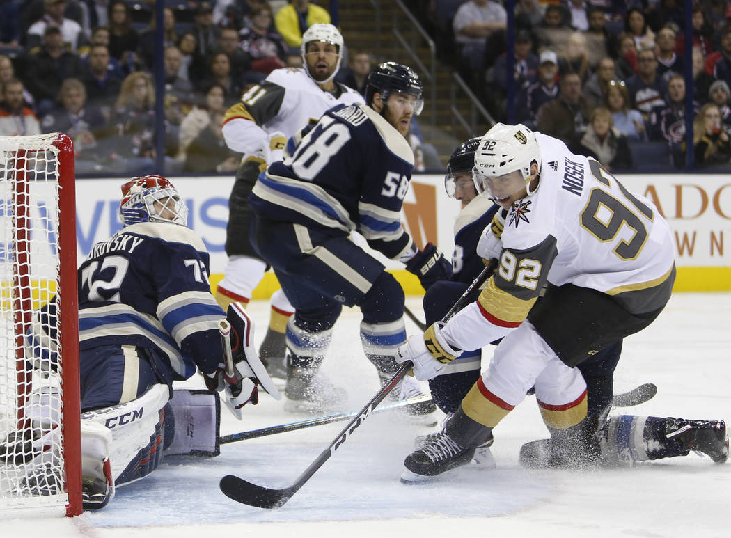 Columbus Blue Jackets' Sergei Bobrovsky, left, of Russia, makes a save against Vegas Golden Knights' Tomas Nosek, right, of the Czech Republic, during the third period of an NHL hockey game Monday ...