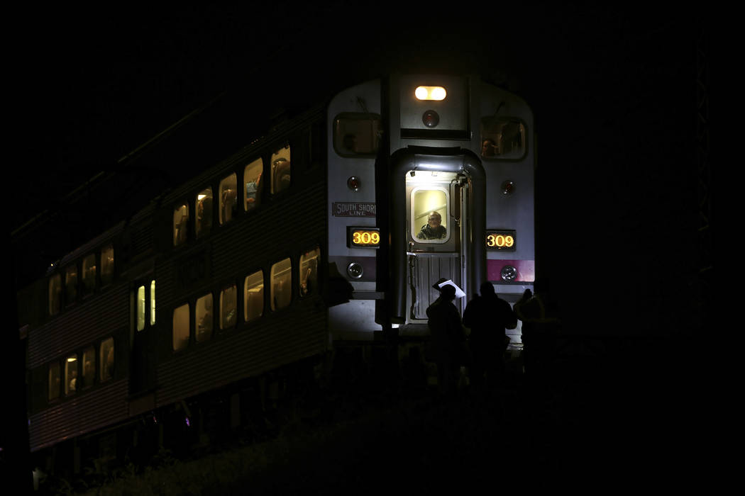 Passengers sit on a train while police officers work the scene where two officers were killed after they were struck by a South Shore train near 103rd Street and Dauphin Avenue on Monday, Dec. 17, ...