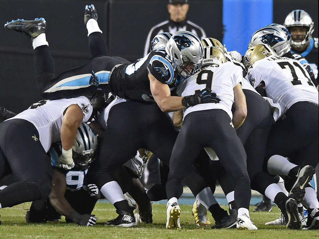 Carolina Panthers' Luke Kuechly, top left, leaps over the line to sack New Orleans Saints' Drew Brees (9) in the first half of an NFL football game in Charlotte, N.C., Monday, Dec. 17, 2018. (AP P ...