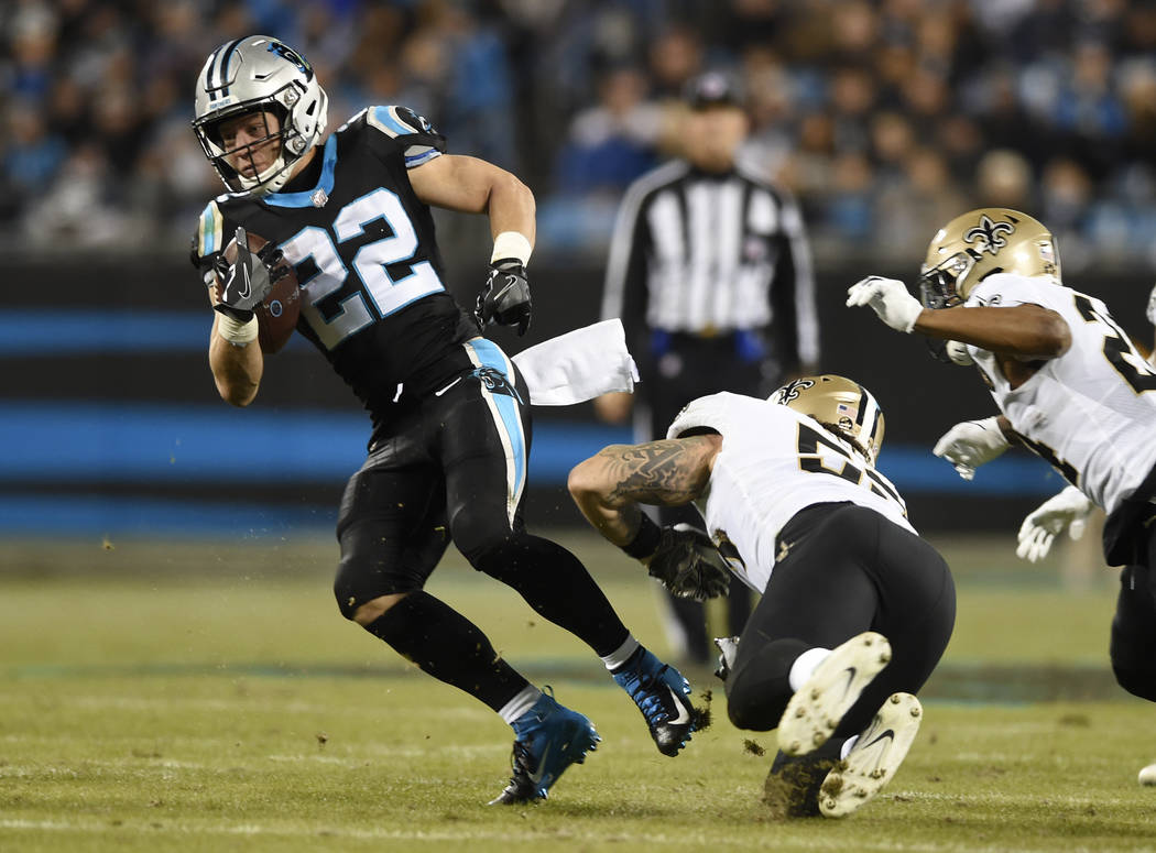 Carolina Panthers' Christian McCaffrey (22) evades a tackle by New Orleans Saints' A.J. Klein (53) in the first half of an NFL football game in Charlotte, N.C., Monday, Dec. 17, 2018. (AP Photo/Mi ...