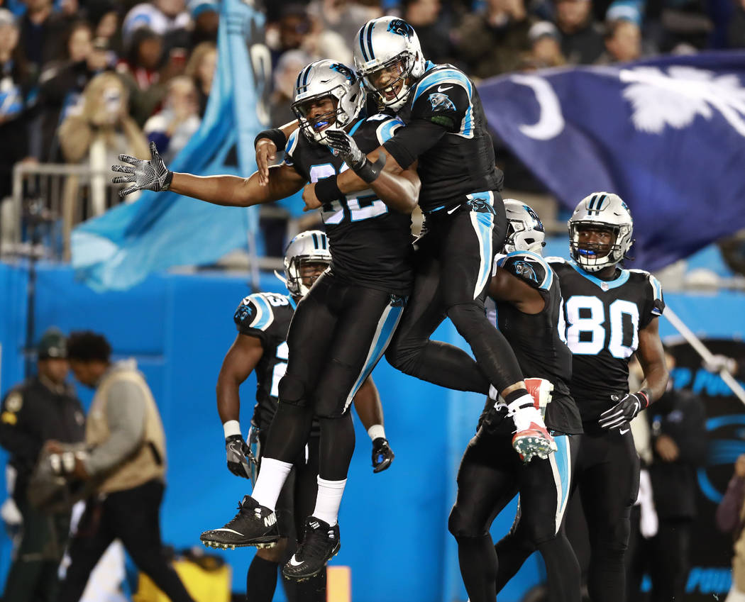 Carolina Panthers' Cam Newton, center right, celebrates with Chris Manhertz (82) after their touchdown against the New Orleans Saints in the first half of an NFL football game in Charlotte, N.C., ...