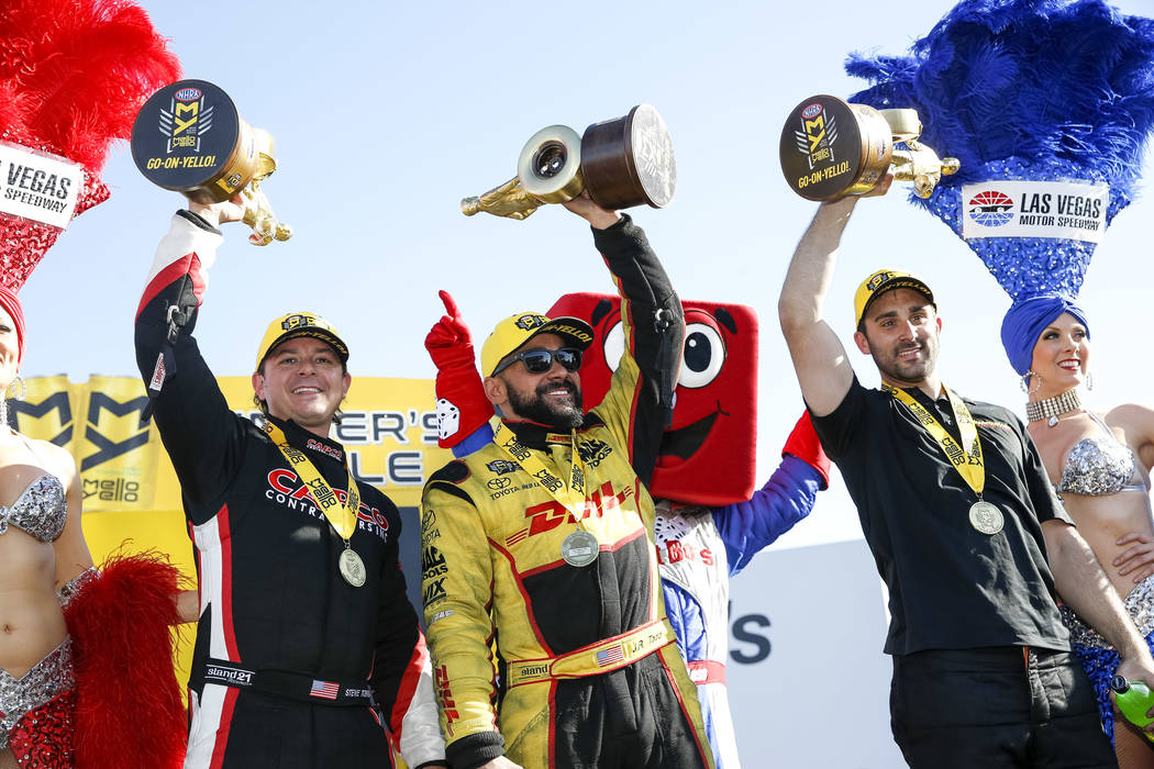 Top Fuel champion Steve Torrence, from left, Funny Car champion J.R. Todd and Pro Stock champion Vincent Nobile pose on stage with their trophies following the DENSO Spark Plug NHRA Four-Wide Nati ...
