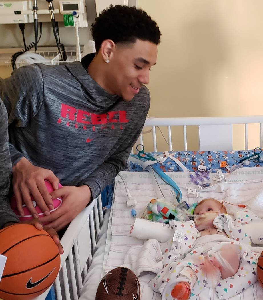 UNLV basketball player Marvin Coleman from Football High School in Henderson visits an unidentified Sunrise Children's Hospital patient during the Annual Gathering hosted by local sports talk radi ...