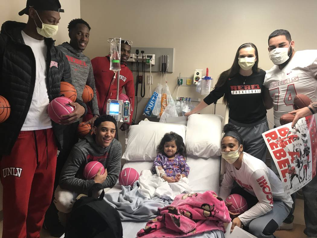 UNLV athletes Ben Coupet, Kris Clyburn, Amauri Hardy (standing left) and Marvin Coleman (crouched left) and Alyssa Anderson, Julio Garcia (standing right) and Nikki Wheatley (crouched right) visit ...