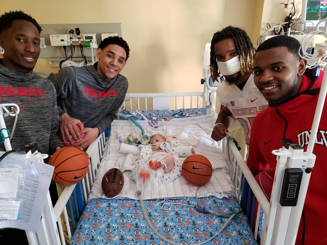 UNLV players Kris Clyburn and Marvin Coleman (left) and Amauri Hardy and Gabe McCoy (right) spend time with a Sunrise Children's Hospital patient named Miles during the Annual Gathering hosted by ...