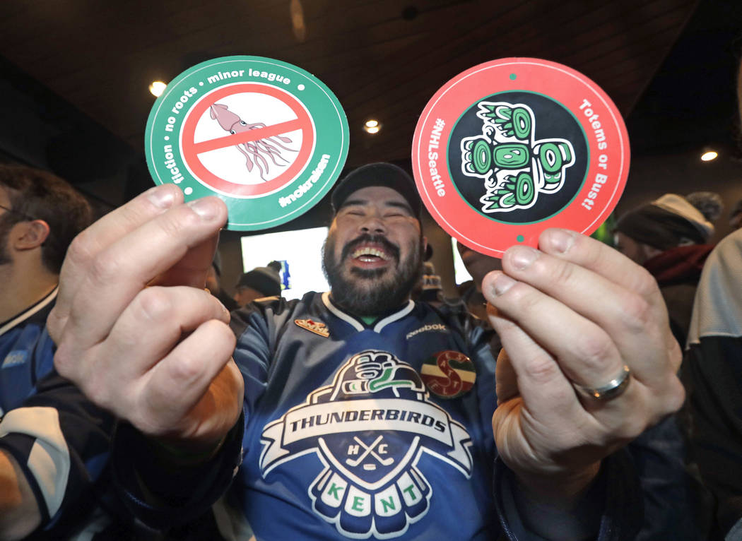 Otto Rogers playfully holds up stickers against the proposed name Kraken and in support of Totems following the announcement of a new NHL hockey team in Seattle, at a celebratory party Tuesday, De ...