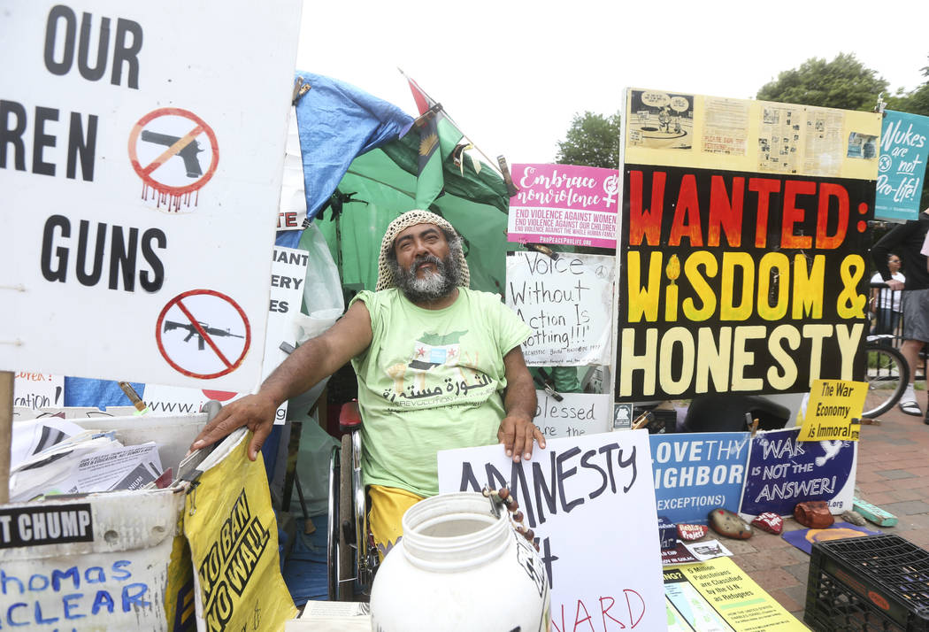 Philipos Melaku-Bello, a peaceful protester, sits with various signs outside of the White House in Washington on Saturday, June 2, 2018. Chase Stevens Las Vegas Review-Journal @csstevensphoto