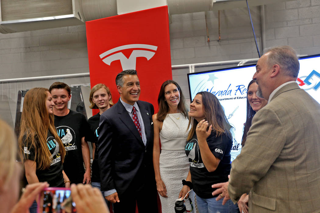 Newlyweds Gov. Brian Sandoval and Las Vegas gaming executive Lauralyn McCarthy pose for photos with the Las Vegas Academy robotics team at an event where Tesla and education leaders revealed new o ...