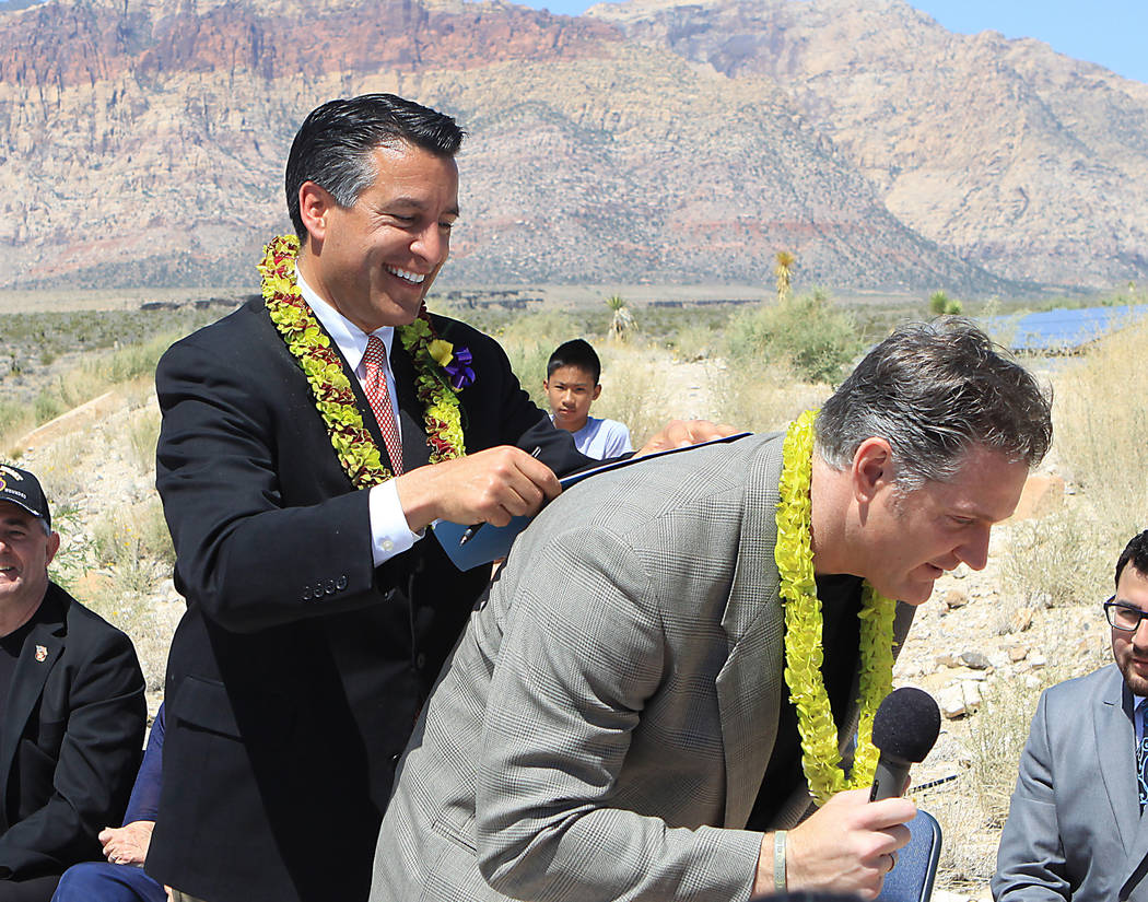 In this May 8, 2012 file photo, Gov. Brian Sandoval uses the back of Defending Freedom founder Phil Randazzo to sign an executive order Saturday at Red Rock Canyon to prioritize and assist militar ...
