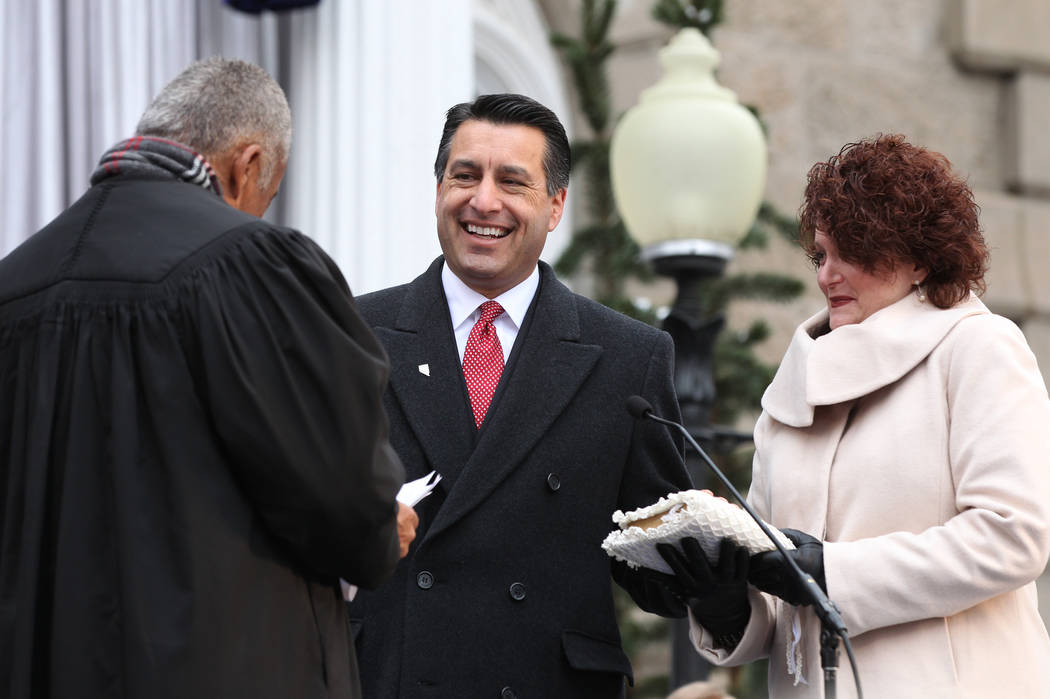 Nevada Gov. Brian Sandoval takes the oath of office from Chief Supreme Court Justice Michael Douglas during Monday's inauguration, Jan. 3, 2011 at the Capitol in Carson City, Nev. Then-first ady K ...