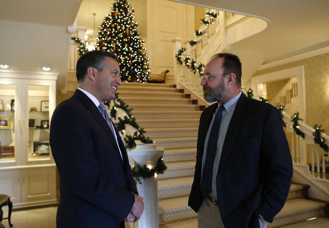 Nevada Gov. Brian Sandoval, left, talks to Nevada Department of Wildlife Director Tony Wasley during a holiday lunch for cabinet and staff members at the Governor's Mansion in Carson City, on Wedn ...