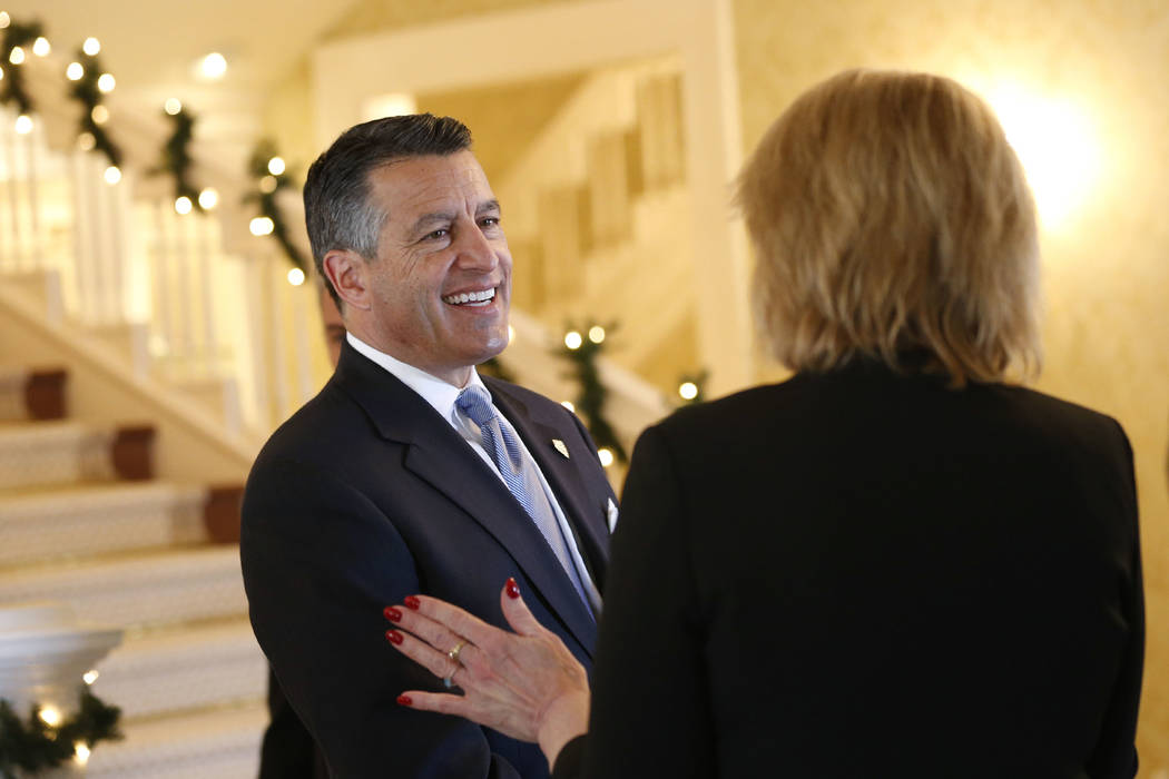 Nevada Gov. Brian Sandoval talks with cabinet and staff members during a holiday lunch at the Governor's Mansion in Carson City, on Wednesday, Dec. 19, 2018. (Cathleen Allison/Las Vegas Review-Jou ...
