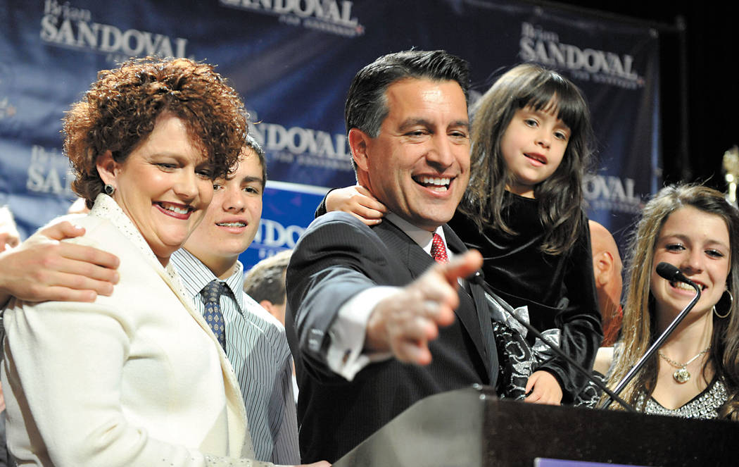 Nevada Gov.-elect Brian Sandoval celebrates his victory with his family at an election night party Tuesday Nov. 2, 2010, in Las Vegas. From left, Kathleen Sandoval, son James, Brian Sandoval holdi ...