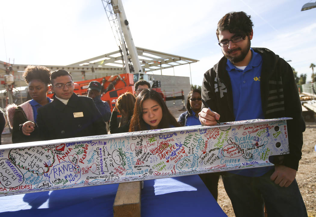 Jeffrey Guadron, right, student government treasurer at College of Southern Nevada, signs a steel beam during a topping off ceremony of the student union building at the CSN North Las Vegas campus ...
