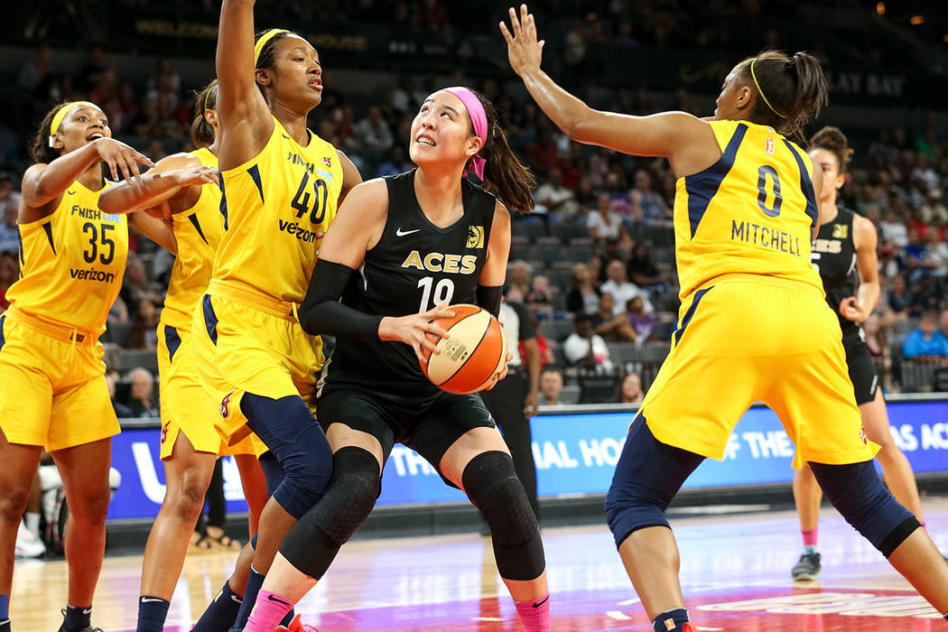 Las Vegas Aces center Ji-Su Park (19) looks for a shot through Indiana Fever defenders Kayla Alexander (40) and Kelsey Mitchell (0) during the second half of a WNBA basketball game at the Mandala ...