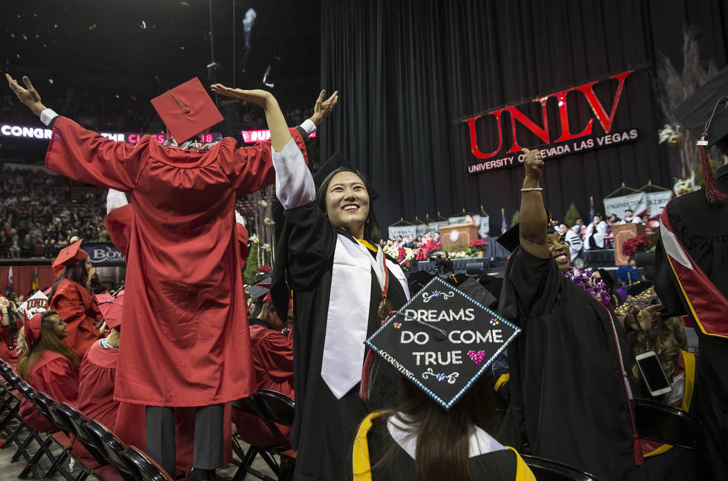 Muzi Liu, middle, waves to her family after earning her masters degree in Accounting at the conclusion of UNLV's winter graduation ceremony on Tuesday, Dec. 18, 2018, at the Thomas & Mack Cent ...